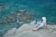 Mujer que se sienta en la roca cerca del mar Imagen de archivo