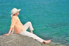 Mujer que se sienta en la roca cerca del mar Fotos de archivo