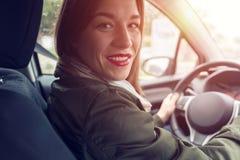 Mujer que se sienta en la rueda del coche Imágenes de archivo libres de regalías