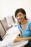 Mujer que se sienta en la sala de ordenadores que pulsa y que sonríe Imagenes de archivo