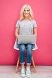 Mujer que se sienta en la silla con el ordenador portátil Imagen de archivo libre de regalías