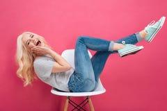 Mujer que se sienta en la silla con las piernas aumentadas Fotos de archivo libres de regalías