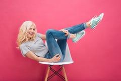 Mujer que se sienta en la silla con las piernas aumentadas Fotos de archivo