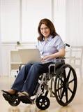 Mujer que se sienta en la silla de rueda que pulsa en la computadora portátil Imágenes de archivo libres de regalías