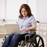 Mujer que se sienta en la silla de rueda que pulsa en la computadora portátil Foto de archivo libre de regalías