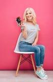 Mujer que se sienta en la silla y que sostiene la cámara de la foto Foto de archivo libre de regalías