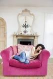 Mujer que se sienta en la sonrisa de la sala de estar Foto de archivo libre de regalías