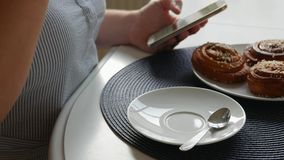 Mujer que se sienta en la tabla, café de consumición con los bollos de canela, café stiring y mirando smartphone