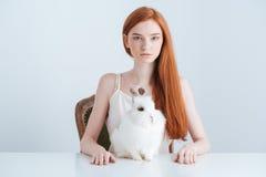 Mujer que se sienta en la tabla con el conejo Fotografía de archivo libre de regalías