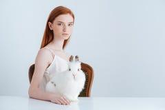 Mujer que se sienta en la tabla con el conejo Imagenes de archivo