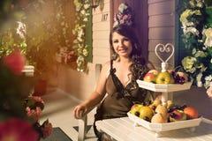 mujer que se sienta en la tabla con el florero de la fruta en él en patio trasero acogedor con las flores color de rosa alrededor Foto de archivo libre de regalías