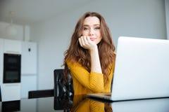 Mujer que se sienta en la tabla con el ordenador portátil Foto de archivo