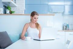 Mujer que se sienta en la tabla con el ordenador portátil y la taza Imágenes de archivo libres de regalías