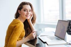 Mujer que se sienta en la tabla con el ordenador portátil y el té de consumición Fotografía de archivo libre de regalías