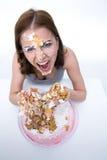 mujer que se sienta en la tabla con la torta en su cara Foto de archivo libre de regalías