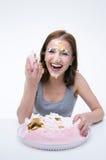 Mujer que se sienta en la tabla con la torta en su cara Fotos de archivo libres de regalías