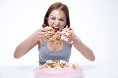 mujer que se sienta en la tabla con la torta en su cara Imagen de archivo