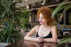 Mujer que se sienta en la tabla con smartphone en restaurante Imagen de archivo