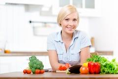 Mujer que se sienta en la tabla de cocina con las verduras fotografía de archivo