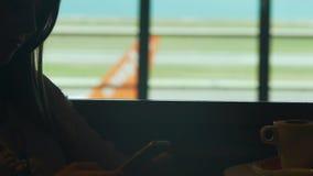 Mujer que se sienta en la tabla en el café del aeropuerto con el teléfono móvil, avión que pasa en la parte posterior metrajes