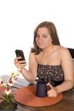 Mujer que se sienta en la tabla en el teléfono celular Imagen de archivo libre de regalías