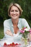 Mujer que se sienta en la tabla en jardín Fotografía de archivo libre de regalías