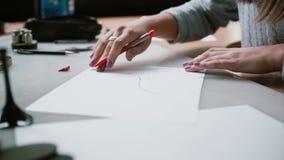 Mujer que se sienta en la tabla en oficina, sosteniendo el lápiz y dibujando el bosquejo de zapatos en el papel Resbalador derech metrajes