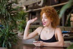 Mujer que se sienta en la tabla en restaurante Imagen de archivo libre de regalías