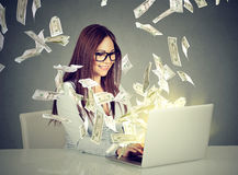 Mujer que se sienta en la tabla usando el trabajo en un ordenador portátil que hace el dinero