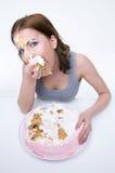 Mujer que se sienta en la tabla y que come la torta Imagenes de archivo