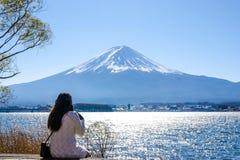 Mujer que se sienta en la tierra en el lago del kawaguchiko, Japón Vista a fotografía de archivo libre de regalías