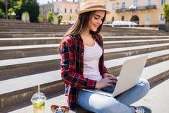 mujer que se sienta en las escaleras de la ciudad y que usa el ordenador portátil Foto de archivo libre de regalías