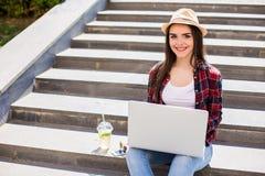 mujer que se sienta en las escaleras de la ciudad y que usa el ordenador portátil Fotos de archivo libres de regalías