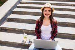 mujer que se sienta en las escaleras de la ciudad y que usa el ordenador portátil Fotos de archivo