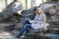 Mujer que se sienta en las rocas Imágenes de archivo libres de regalías