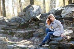Mujer que se sienta en las rocas Imagen de archivo libre de regalías