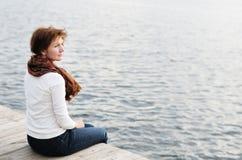 Mujer que se sienta en las tarjetas de madera por el agua Imágenes de archivo libres de regalías