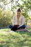 Mujer que se sienta en lecho en hierba verde Fotografía de archivo