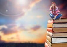 Mujer que se sienta en los libros apilados por el cielo de la puesta del sol fotografía de archivo