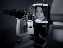 Mujer que se sienta en máquina del óptico imagenes de archivo