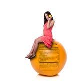 Mujer que se sienta en naranja con la escritura de la etiqueta de la nutrición imagen de archivo