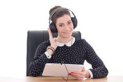 Mujer que se sienta en oficina y música que escucha Imagenes de archivo
