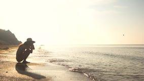 Mujer que se sienta en orilla soleada almacen de metraje de vídeo