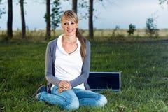 Mujer que se sienta en parque Imagen de archivo libre de regalías