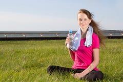 Mujer que se sienta en parque con la toalla y la botella Fotos de archivo libres de regalías
