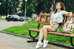 Mujer que se sienta en parque del banco Imagen de archivo