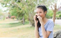 Mujer que se sienta en piedra usando un teléfono móvil Foto de archivo