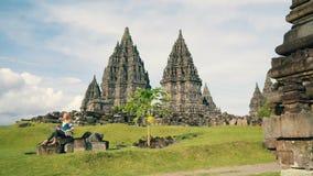 Mujer que se sienta en piedras delante del templo de Prambanan almacen de metraje de vídeo