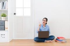Mujer que se sienta en piso en casa usando el ordenador Imagenes de archivo