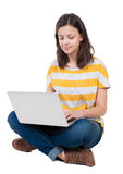 Mujer que se sienta en piso con el ordenador portátil Imágenes de archivo libres de regalías